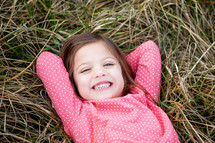 little girl lying in grass
