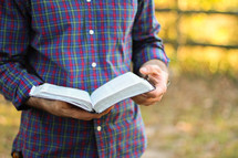 man standing reading a Bible