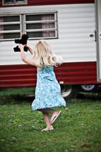 little girl running holding a teddy bear