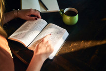 a woman reading a Bible and writing in a journal