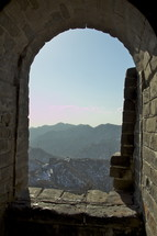 looking out a window at a mountain view from the Great Wall