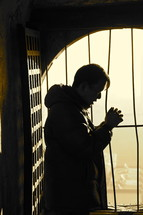 Silhouette of a Chinese church leader in prayer in front of a barred window