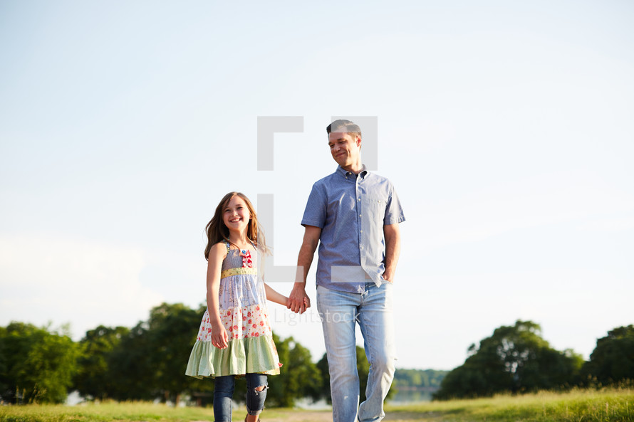 a father walking holding hands with his daughter