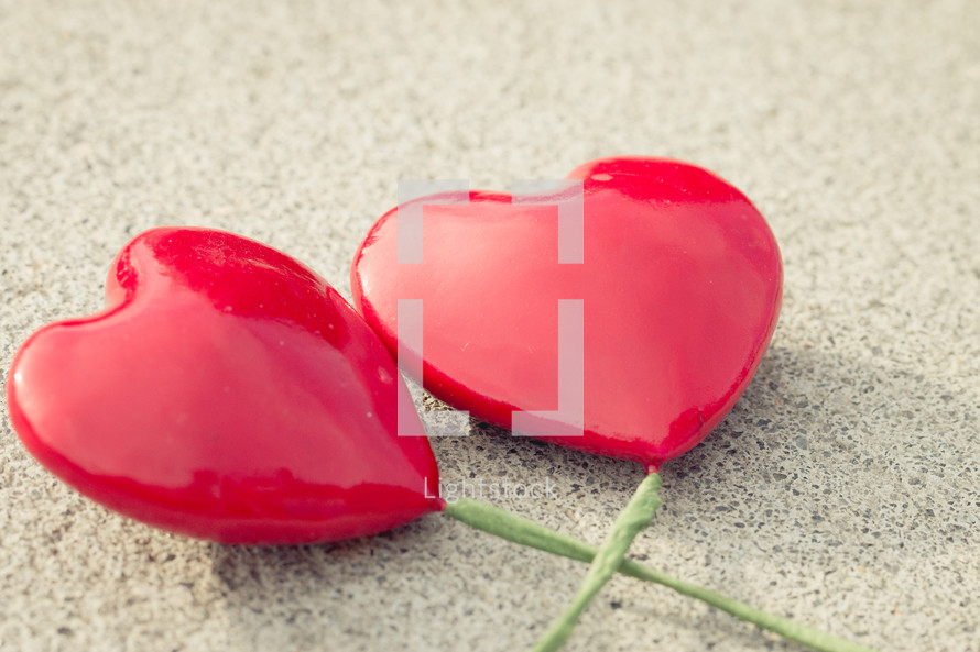 Solid red hearts with green stems on a textured background