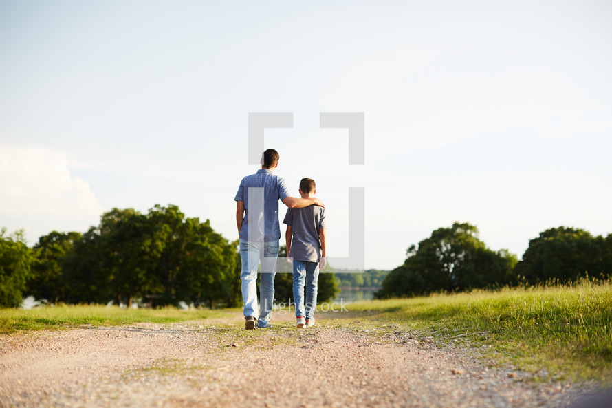 a father and son walking and talking together outdoors