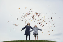 sisters tossing fall leaves in the air