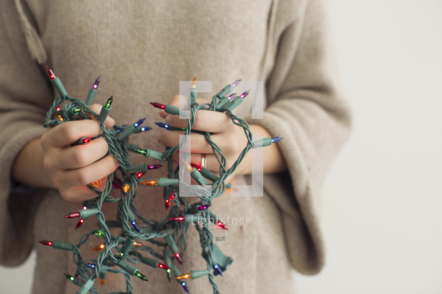a man holding tangled Christmas lights