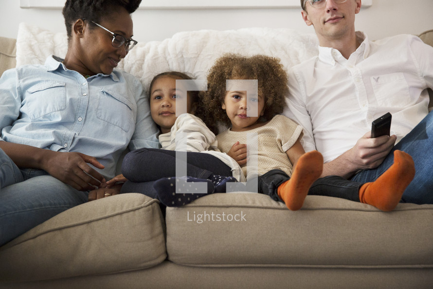 a family sitting on a couch watching tv together.