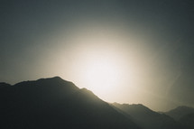sun rising from behind a mountain