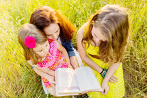 mother and daughters reading a Bible together outdoors