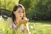 A young woman in a field blowing dandelion seeds.