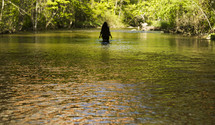 A woman wading in a river.