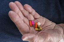 pills in the hand of an elderly woman