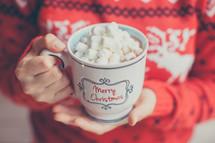 a woman holding a mug of hot cocoa