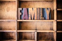 "Wooden letters spelling ""family"" on a wooden bookshelf."