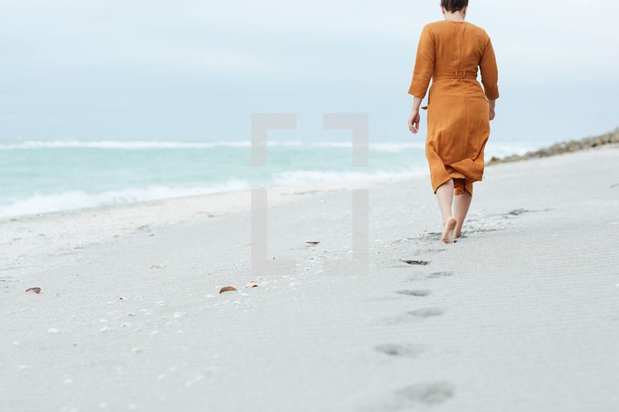 a woman walking on a beach looking out at the water