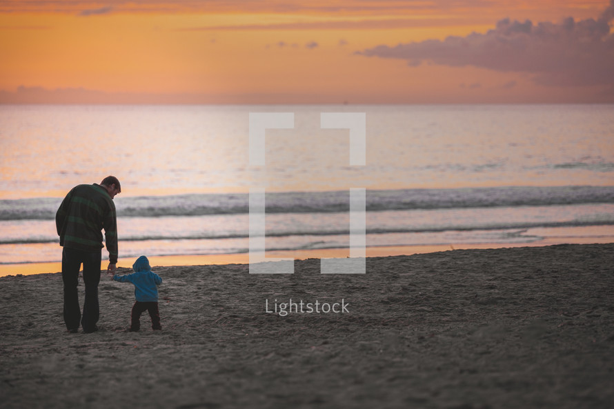 father and toddler son on a beach in fall