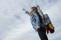 woman standing in a jetpack, figuring out how to get to Heaven