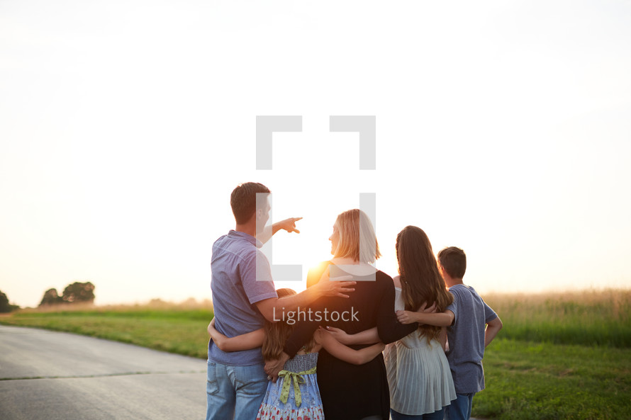 a family standing outdoors on a rural road