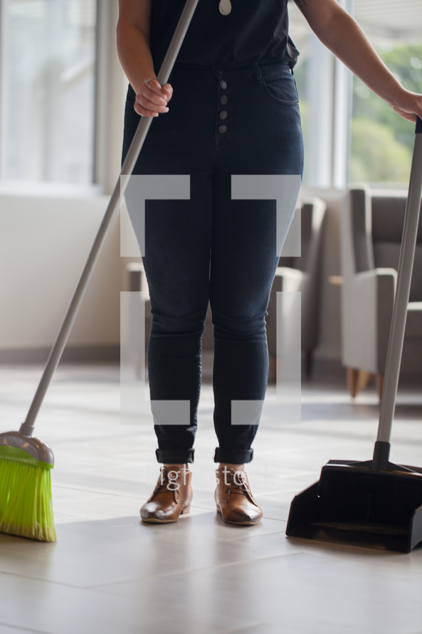 a woman holding a broom and dust pan