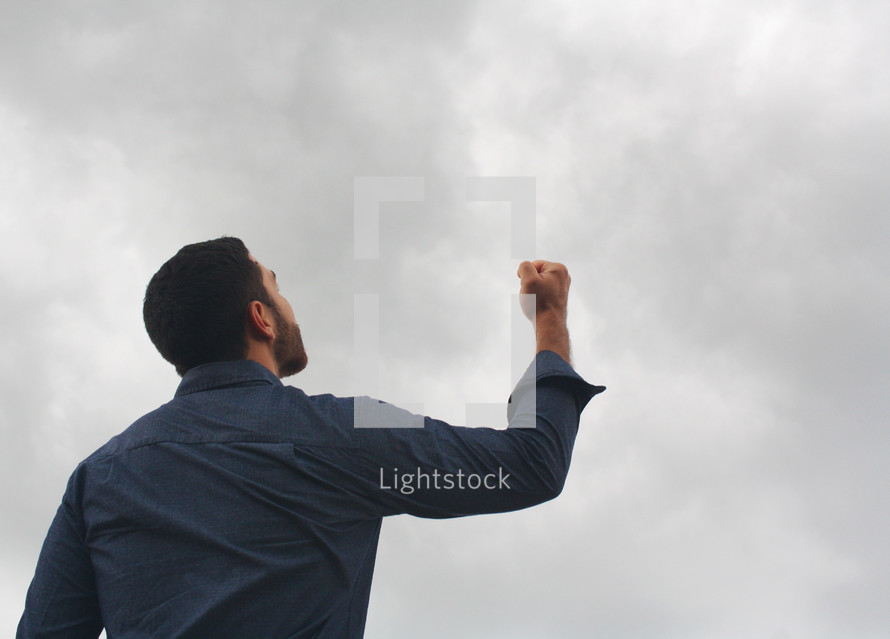 a man with a raised fist looking up to God