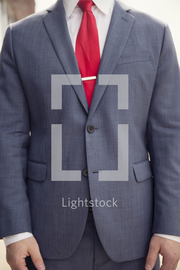 torso of a business man with his hand at his side
