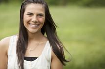 Smiling ethnic girl standing outside.