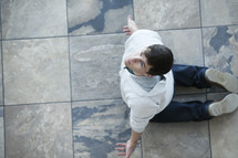 Aerial view of a man on his knees om tile, surrendering to God.