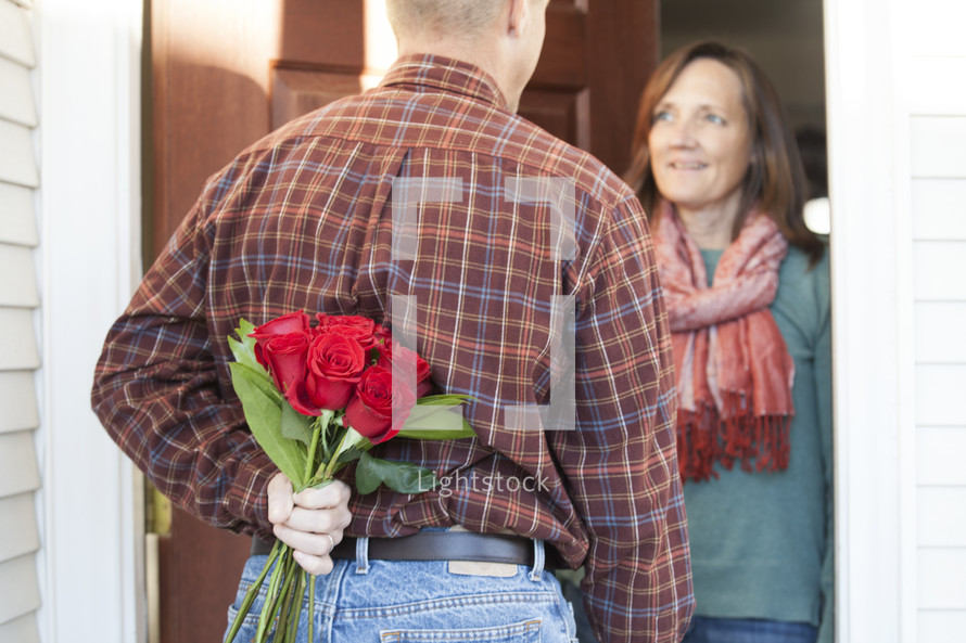Man surprising his wife with flowers.
