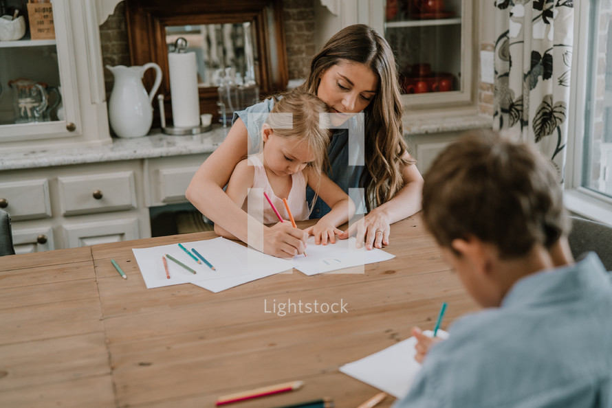 a mother coloring with her children