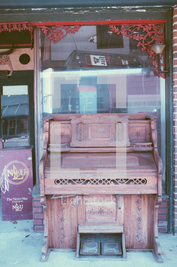 old piano in front of an antique store