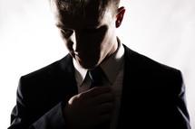 a man straightening his tie