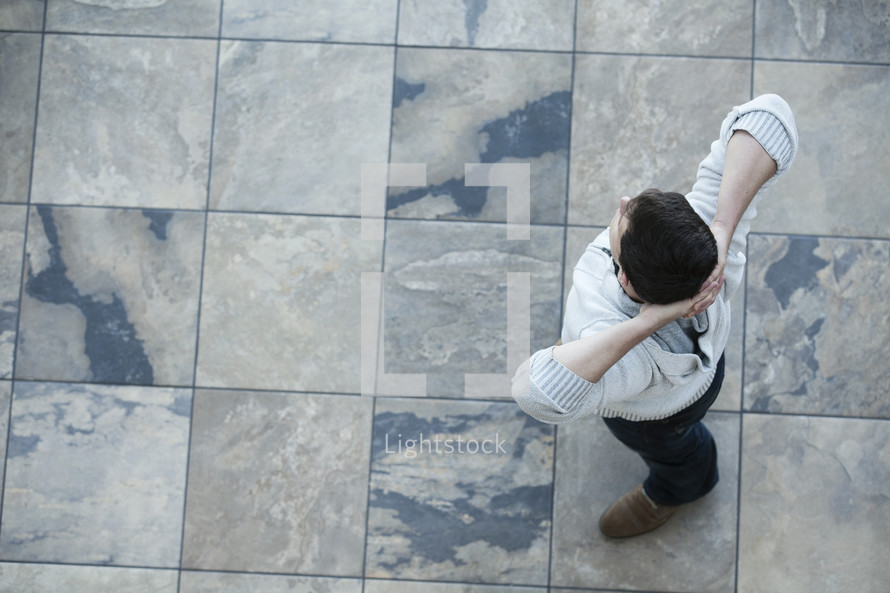 Aerial view of a man standing on tiles with his hands behind his head.