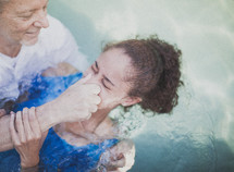 Man baptizing a girl in a pool of water.
