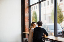 a couple on a date sitting in a window