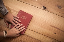 promise with hands on a Bible