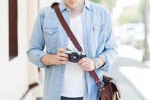 man holding a camera and shoulder bag