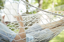 man reading a Bible in a hammock