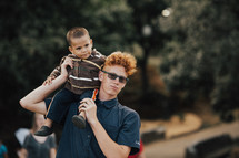 man with a toddler on his shoulders