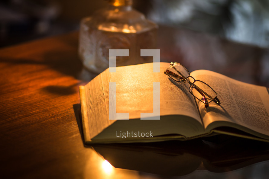 reading glasses on an open Bible