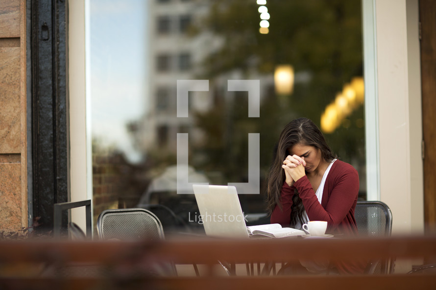 a young woman sitting at an outdoor table with laptop and head bowed in prayer