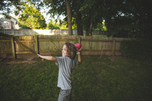 A boy child throwing a football in the backyard.