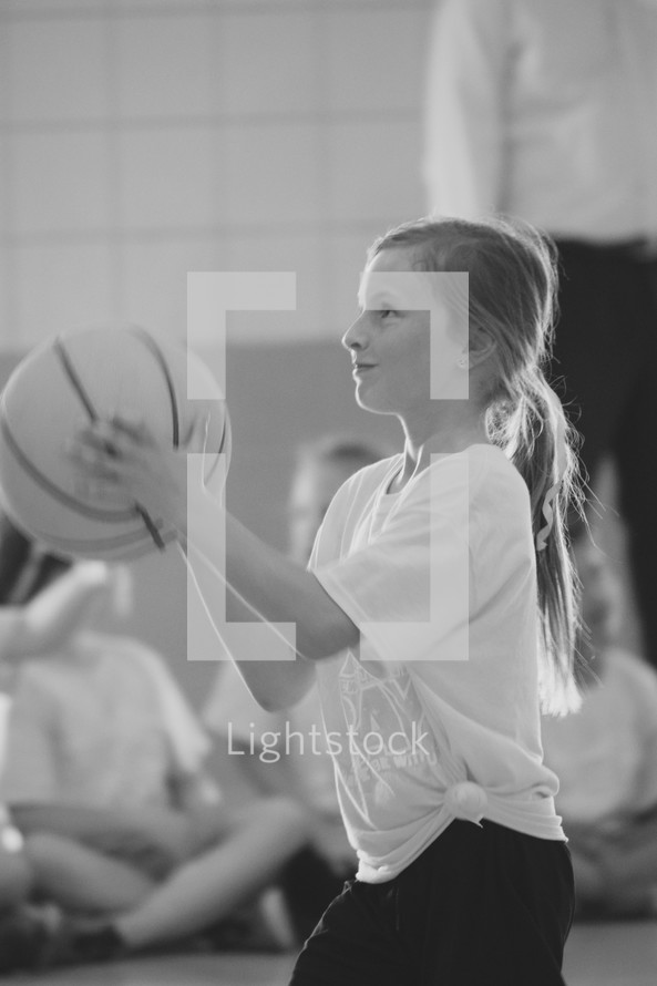 a little girl shooting a basketball