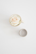 rose in a tea cup and votive candle
