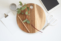clip, blank paper, scissors, eucalyptus twigs, wood cutting board, tablet, votive candle