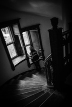 woman standing in a stairway looking out a window