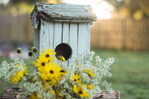 birdhouse and yellow flowers