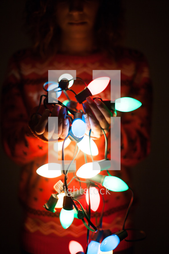 woman holding a string of glowing Christmas lights