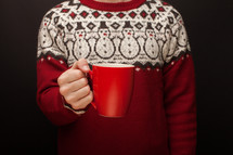 a man in a Christmas sweater holding a mug