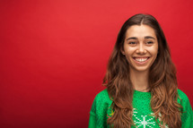 a headshot of a smiling woman in a Christmas shirt